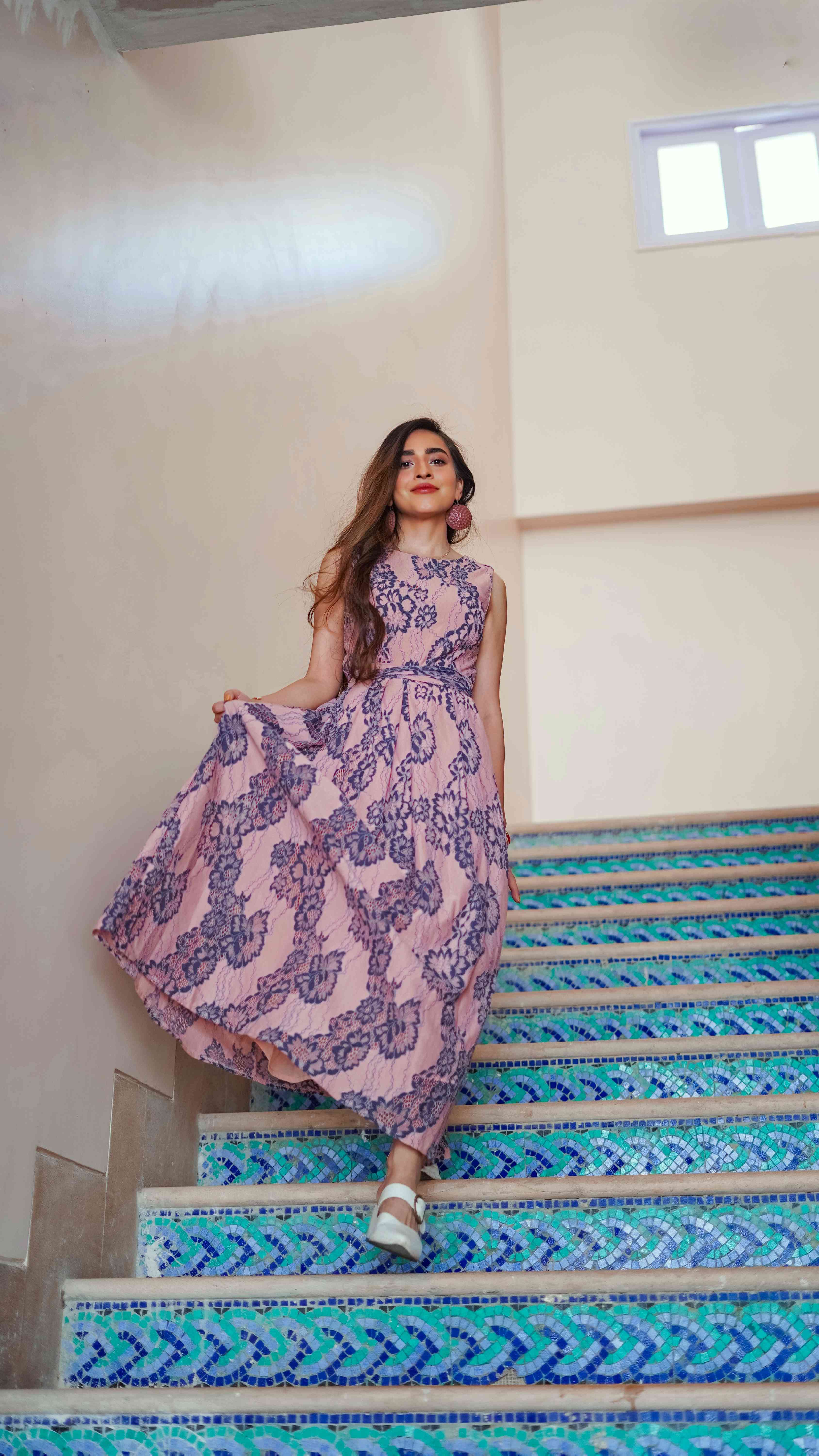pink floral lace maxi dress walking down blue tile stairs